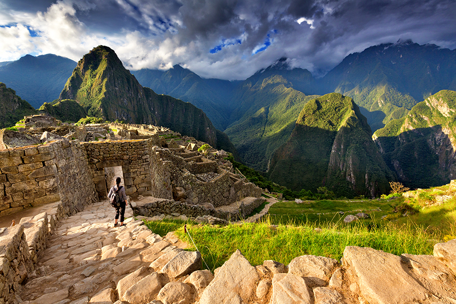 Back view of female tourist descending stairs overlooking Machu Picchu ruins at sunset, Peru