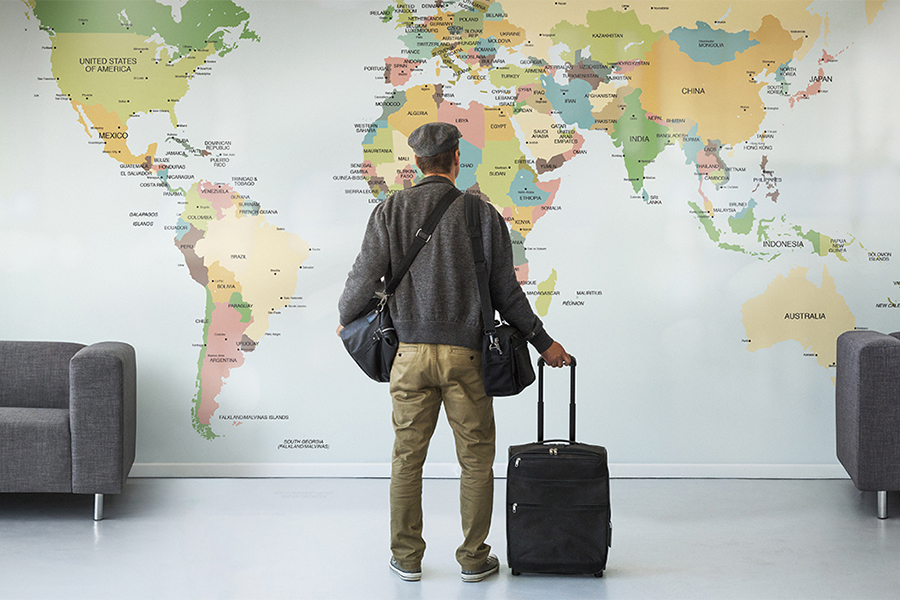 Man with luggage looking at large wall map